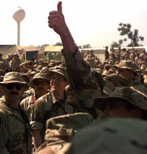 President George Bush gives the thumbs up sign to the troops upon his arrival at the American Embassy Compound