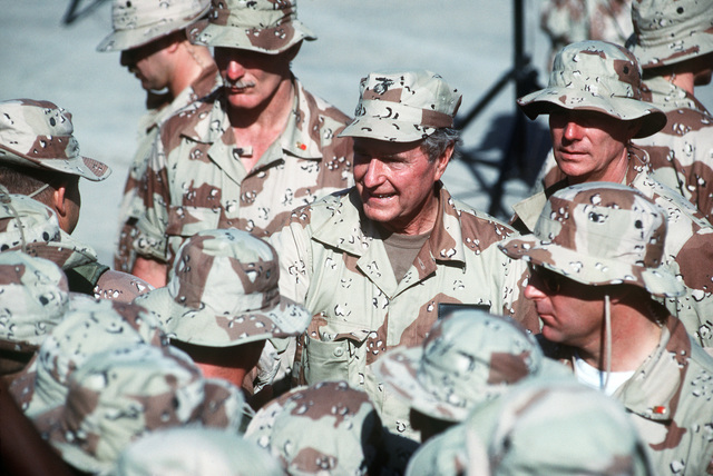President George Bush shakes hands and speaks to individuals as he walks through a crowd of U.S. troops at the airport
