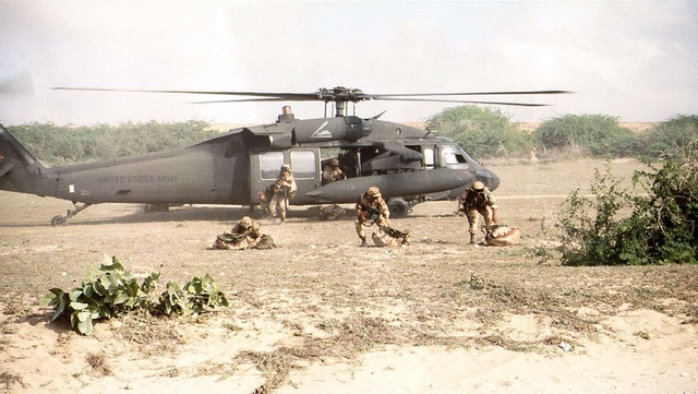 "Right side profile shot of a US Army UH-60 ""Black Hawk"" helicopter on the ground at Merca, Somalia. Five Soldiers from the 2nd Brigade, 10th Mountain Division, Fort Drum, New York jump out of the helicopter for the air assault into Merca from Baledogle, Somalia on 31 Dec. 92. This mission is in direct support of Operation Restore Hope"