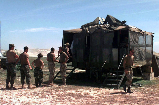A line of US Joint Task Force personnel forms at one of two mobile kitchen trailers at Mogadishu Airport, set up by the 823rd Red Horse Squadron, Hurlburt Field, Florida. The kitchens feed 300 to 350 Air Force personnel and some 400 to 500 Marines a day using 36 to 40 boxes of T-rations a day. This mission is in direct support of Operation Restore Hope