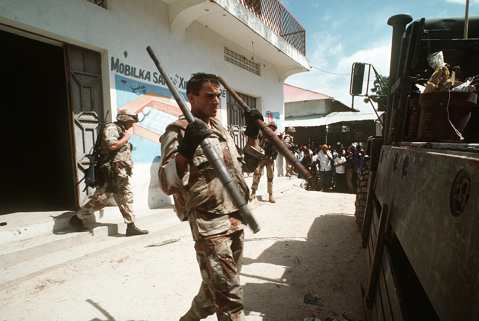 A Marine carries machine gun barrels confiscated during the
