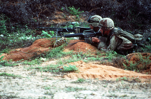 A pair of Marines from Task Force Mogadishu are ready to provide covering fire during a raid on a weapons cache during the multinational relief effort Operation Restore Hope. They are armed with a 5.56mm M-16A2 rifle and a 7.62mm M-60E3 lightweight machine gun