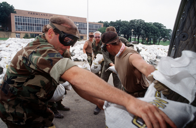 Air National Guard troops load sand bags onto a UH-1 helicopter at the Farmland Insurance Building. The sand bags will be used to fortify levees and to build walls to hold back the advancing flood waters.(Exact date unknown)
