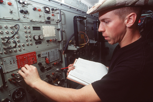 AIRMAN 1ST Class Kevin Finley, satellite communications specialist, 5th Combat Communications Group, Robins AFB, GA, checks the power level of a high power amp