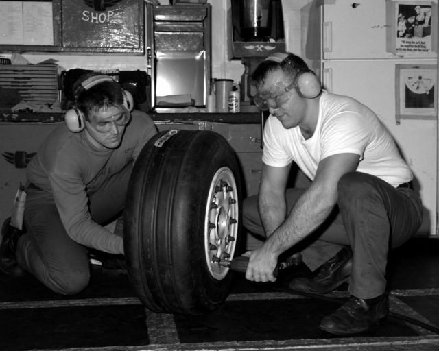 Aviation Structural Mechanic S (Structures) (AMS3) Tracey Perman, left, and AMS3 Aaron Long assemble an aircraft landing gear wheel assembly aboard the nuclear-powered aircraft carrier USS NIMITZ (CVN-68) during WestPac '93