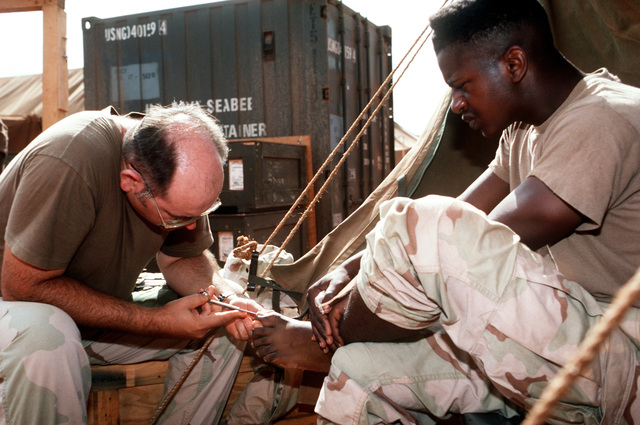 CHIEF Hospital Corpsman Meredith Morris treats Mess SPECIALIST/SEAMAN Apprentice Robert Shepard for an ingrown toenail at the medical tent during sick call for members of Naval Mobile Construction Battalion 1 (NMCB-1). The unit is stationed in the region during Operation Restore Hope relief efforts