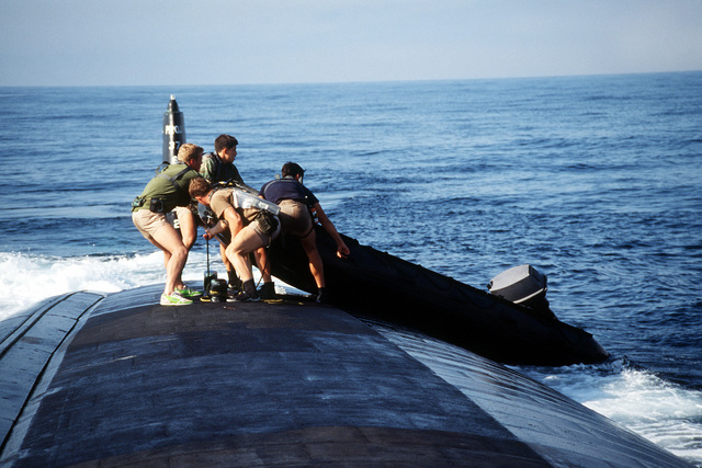 Four members of SEAL Team One are shown recovering a Zodiac boat on the aft section of the nuclear-powered attack submarine USS LOUISVILLE (SSN-724) at the conclusion on Operation Varsity Swimmer '93 off the coast of southern California