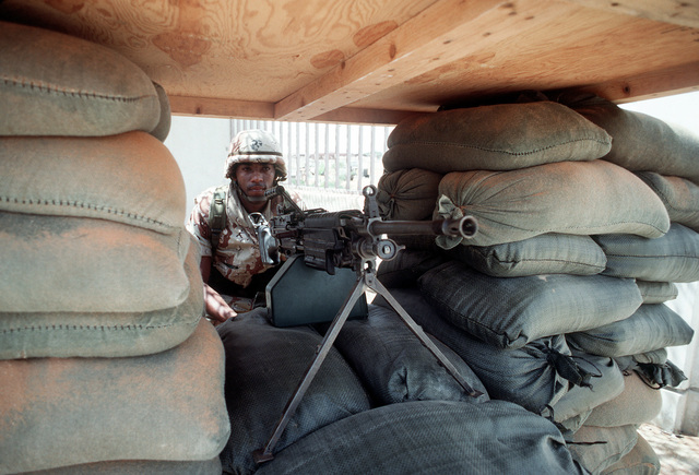 LCPL Aaron Gobert, a member of K Company, 3rd Battalion, 9th Marine Regiment, mans a 5.56mm M-249 squad automatic weapon (SAW) in a sandbagged bunker guarding an entrance to the Joint Task Force Somalia headquarters. The headquarters was established at the former U.S. Embassy compound during the multinational relief effort Operation Restore Hope