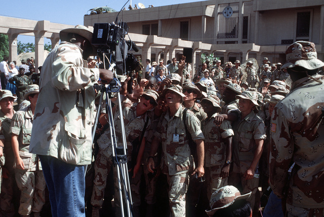 Marines gather in front of a television camera during a live broadcast following President George Bush's remarks at the Joint Task Force Somalia headquarters. The headquarters was established at the former U.S. Embassy compound during the multinatinoal relief effort Operations Restore Hope