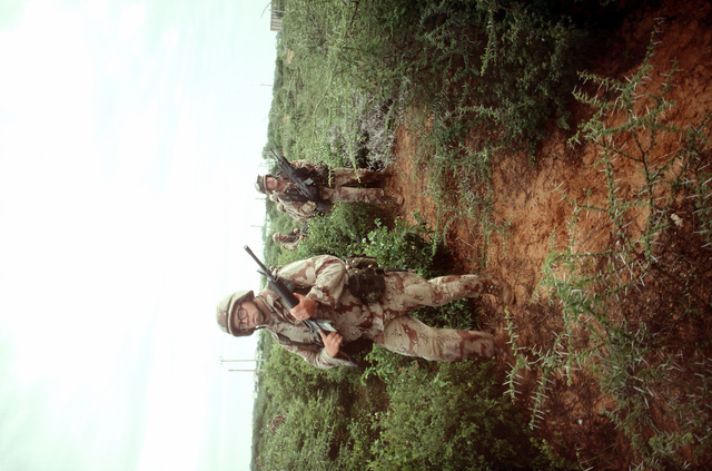 Marines of Task Force Mogadishu advance toward the entrance of a weapons cache during the multinational relief effort Operation Restore Hope