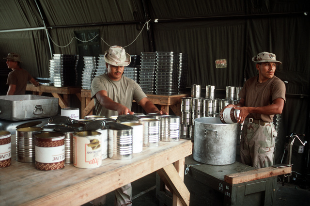 Marines of the 1ST Force Service Support Group prepare part of the evening meal served at the Joint Task Force Somalia headquarteres. The headquarters was established at the former U.S. Embassy compound during the multinational relief effort Operation Restore Hope