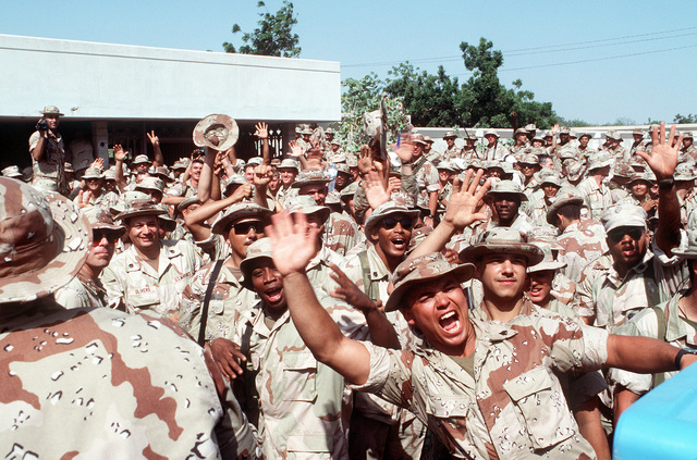Marines wave to a television camera during a live broadcast following President George Bush's remarks at Joint Task Force Somalia headquarters. The headquarters was established at the former U.S. Embassy during the multinational relief effort Operation Restore Hope