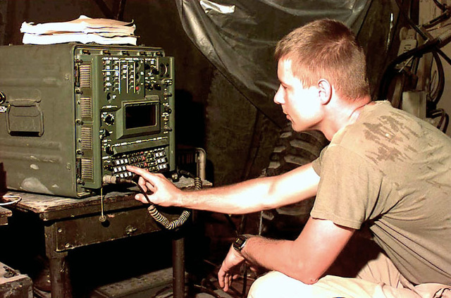 Medium Close-up, left side profile, of US Air Force SSGT Rick Robinson from the 52nd CCS, Robins Air Force Base, Georgia. He reaches out and touches with his right hand a SB 3865 Tactical Telephone Switch at the US Embassy in Mogadishu, Somalia. The 52nd provides the communications support for the Air Force Air Mobility Element deployed to Mogadishu, Somalia. This mission is in direct support of Operation Restore Hope