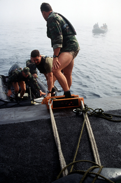 Members of SEAL Team, one climb up a jacobs ladder onto the deck of the nuclear-powered attack submarine USS LOUISVILLE (SSN-724) as part of Operation Varsity Swimmer '93 off the coast of southern California. A second zodiac boat loaded with SEAL team members can be seen approaching the Louisville from out of the fog