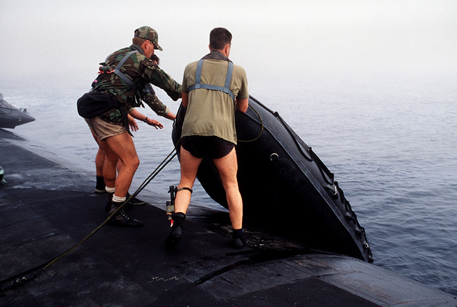 "Navy divers from SEAL Team One are show launching a Zodiac boat from the aft section of the nuclear-powered attack submarine USS LOUISVILLE (SSN-724) as part of ""dry deck"" launches and recoveries during Operation Varsity Swimmer '93 off the coast of Southern California"