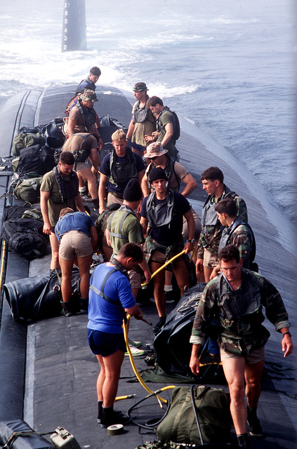"Navy divers from SEAL Team One, based at Naval Amphibious Base Coronado, are shown preparing for ""dry deck"" launches and recoveries from the nuclear-powered attack submarine USS LOUISVILLE (SSN-724) off the coast of southern California during Operation Varsity Swimmer '93"