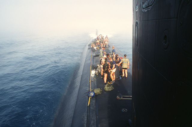 "Navy divers from SEAL Team One, based at Naval Amphibious Base Coronado, are shown preparing for ""dry deck"" launches and recoveries from the aft section of the nuclear-powered attack submarine USS LOUISVILLE (SSN-724) off the coast of southern California during Operation Varsity Swimmer '93"