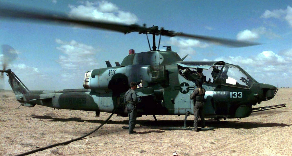 """Right Side profile of a US Marine AH-1 """"Cobra"""" helicopter from VMGR-352, El Toro, Marine Corps Air Station, California, being refueled from a US Marine KC-130 Refueling Plane, not shown. Two Marines from the KC-130 crew stand next to the AH-1 as the refueling takes place. The refueling allows the helicopters to return to escorting a food convoy (not shown) and preventing them from being robbed or harassed by Somali bandits. This mission is in direct support of Operation Restore Hope"""