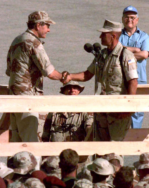 Right side profile of US President George Bush as he reaches out to shake the hand of US Marine LGEN Robert Johnston, Commander, Joint Task Force Operation Restore Hope, on a wooden podium. Multi-national forces are seen in the foreground facing the dignitaries. Johnston thanked Bush for his support of the military during his term as President. The President visited Somalia to show is gratitude to those involved in the mission of Operation Restore Hope