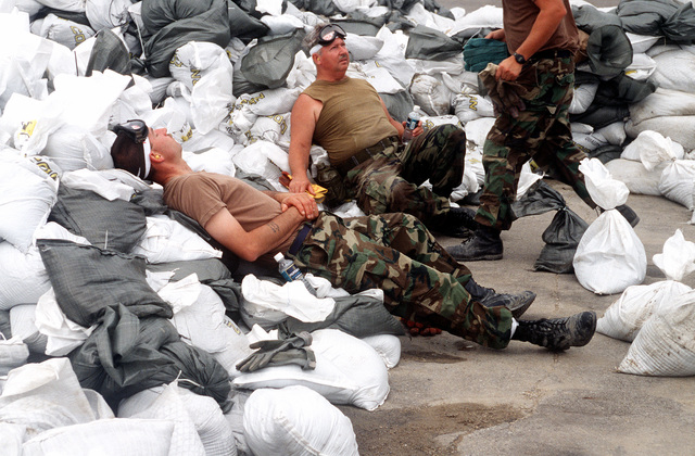 SGT. Mike Shean and another Air National Guard troop takes a needed break from loading fifty pound sand bags onto helicopters at the Farmland Insurance parking lot.(Exact date unknown)