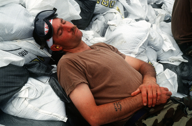 SGT. Mike Shean from the Air National Guard takes a needed break from loading fifty pound sand bags onto helicopters at the Farmland Insurance parking lot.(Exact date unknown)