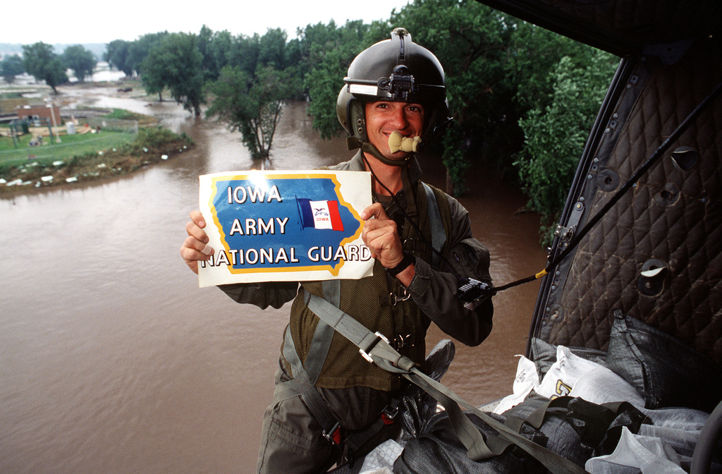 """STAFF SGT. Fred Miller from the Army National Guard stands on the edge of a UH-1 helicopter as he holds a sign that says """"Iowa Army National Guard."""" The helicopter is in flight and the flood waters can be seen in the background.(Exact date unknown)"""