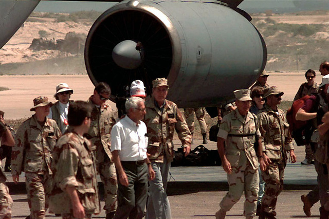 Straight on, long shot, of US President George Bush, center, as he walks with his entourage away from a US Air Force C-141 Starlifter. To the President's left is US Marine LGEN Robert Johnston, Commander, Joint Task Force Operation Restore Hope. Several others walking with the President are unidentifiable