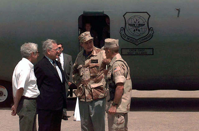 Straight on, medium shot of US President George Bush wearing a desert camouflaged BDU top and cap. He's speaking with US Marine LGEN Robert Johnston, Commander, Joint Task Force Operation Restore Hope, right. Two other unidentifiable men in civilian clothes stand with them at the left of the frame. An opened left side entrance to a US Air Force C-141 Starlifter is seen in the background. Two members of the C-141 flight crew stand in the entrance looking out for the President. President Bush is in Mogadishu to visit the troops on duty supporting the United Nations operations in the area