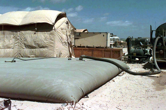 Straight on shot of a Tactical Water Distribution System (TWDS). The large bladder sits on the ground in front of a shower tent set up at Mogadishu Airport by the 823rd Red Horse Squadron, Hurlburt Field, Florida, for use by US Air Force Personnel. A water truck is partially seen at the right pumping water into the TWDS. This mission is in direct support of Operation Restore Hope