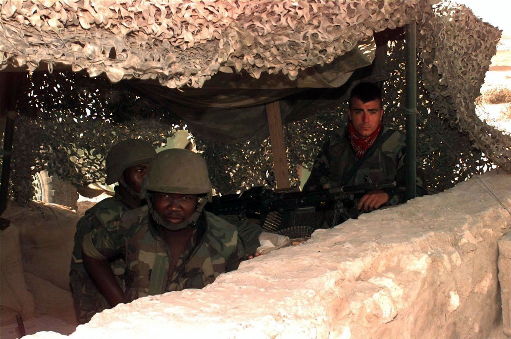 Straight on shot of Jim Boyle, Law Enforcement SPECIALIST with the 86th Security Police Squadron, Ramstein Air Base, Germany, at right along with LCPL M. Mosothwawe and PVT T. Willie, both of the Botswana United Nations Force, face the camera as they all sit in a bunker at the Entry Control Point on the western perimeter of Mogadishu Air Port. They all sit behind a stonewall. The bunker is covered with camouflaged netting. One of the Botswana Soldiers mans a M60 machine gun. This mission is in direct support of Operation Restore Hope