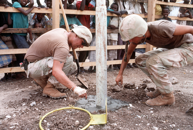 Two members of Naval Mobile Construction Battalion 1 (NMCB-1) put their initials in the concrete footing they just poured during the multinational relief effort OPERATION RESTORE HOPE. The Seabees are installing a basketball hoop in the playground of a local school as part of a civic action project
