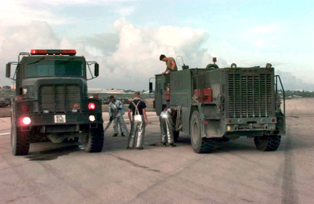 US Air Force fire department crews assigned to safeguard Mogadishu Airport refill their P-19 Fire Truck from a P-18 2000 gallon tanker. The tanker is left facing the camera and the fire truck is right facing away from the camera. Fire crews from McChord, Travis, and Charleston Air Force Bases responded to the scene of an Italian helicopter accident (not shown) and foamed the area around the helicopter where fuel has leaked from it. The runway was closed for approximately three hours. This mission is in direct support of Operation Restore Hope