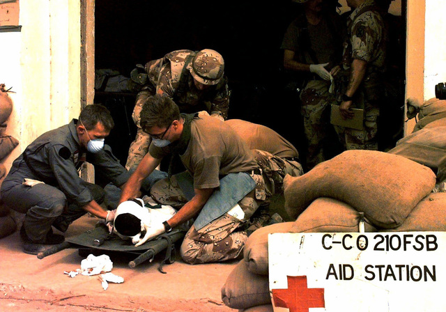 """US Army medical personnel from """"C"""" Company, 210 Forward Support Battalion, 10th Mountain Division, Fort Drum, New York, attend to a head wound suffered by a Somali in an auto accident just outside Baledogle. Eight Somali nationals (not shown) were injured in the accident and rushed to the aid station. Four of the most seriously injured were treated by soldiers to stabilized them and then transferred to Mogadishu (not shown). This mission is in direct support of Operation Restore Hope"""