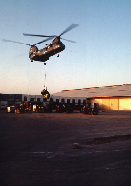 A CH-46 Sea Knight helicopter from the USS Niagara Falls sling load supplies in the port of Mogadishu. The supplies flown in from the USS Niagara Falls were to replenish the Maritime Prepositioning Ships docked in the port. The Maritime Prepositioning Ships are unloading military supplies for the US Marines who are part of the Unified Task Force