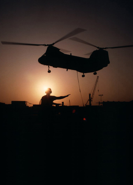 A silhouette of a CH-46 Sea Knight helicopter from the USS Niagara Falls as it drops supplies in the port. The supplies flown in from the USS Niagara Falls were to replenish the Maritime Prepositioning Ships docked in Mogadishu. The Maritime Prepositioning Ships are unloading military supplies for the US Marines who are part of the Unified Task Force