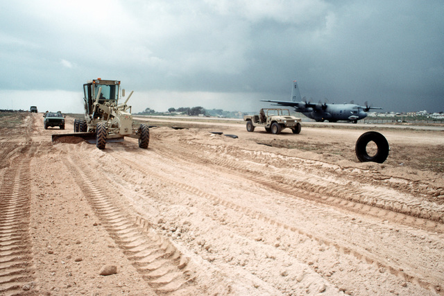A member of Naval Mobile Construction Battalion 40 operates a motor grader while improving an access road next to a runway. The Seabees have been deployed as part of the U.S. involvement in the multinational relief effort OPERATION RESTORE HOPE. An Air Force C-130 Hercules aircraft is on the runway in the background