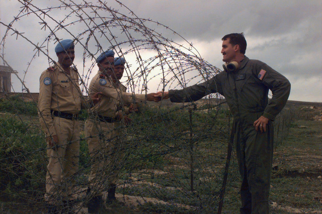 Boatswain's Mate First Class (Surface Warfare) James B. Odell, (right), reaches through the concertina wire to shake hands with members of the Pakistani Army. PETTY Officer Odell is a loadmaster on an Air Cushioned Landing Craft (LCAC) from Assault Craft Unit Five (ACU-5), Swift Intruders. The ACU-5 from Camp Pendleton, CA, deployed on board the USS MOUNT RUSHMORE is part of the operation. The Pakistani Army is part of the United Nation's Forces in Somalia