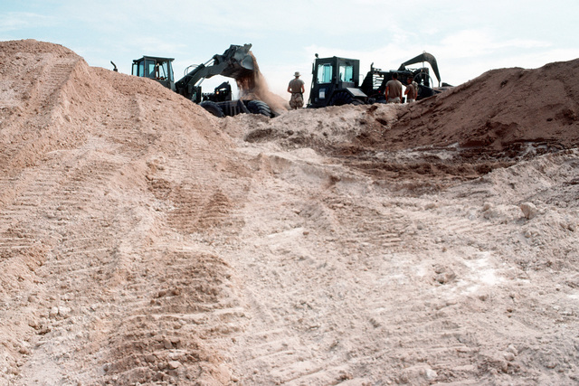 Members of Naval Mobile Construction Battalion 40 use heavy construction equipment to improve an access road next to a runway during the multinational relief effort OPERATION RESTORE HOPE