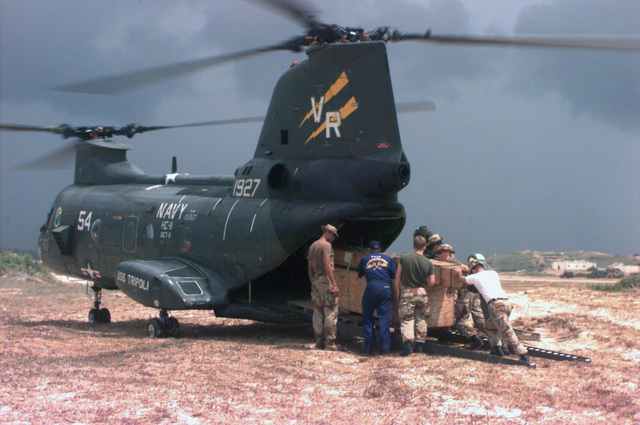 "Sailors and Marines load crates of cargo into a CH-46 ""Sea Knight"" helicopter at the airport. The ""Sea Knight,"" from Helicopter Cargo Squadron Eleven (HC-11) of Naval Air Station (NAS) North Island, San Diego, CA, deployed aboard the USS TRIPOLI. The units are part of Joint Task Force Somalia"