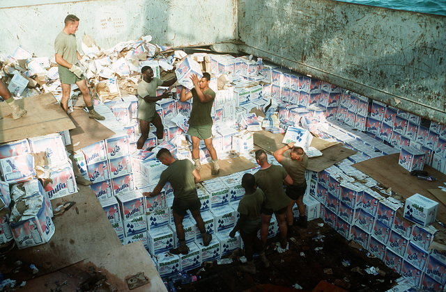 Members of the 1ST Landing Support Battalion (LSB), 1ST Marine Division, unload crates of bottled water from a ship moored in the city's harbor during the multinational relief effort Operation Restore Hope