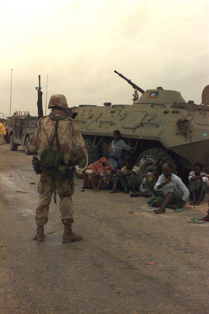 A US Marine from Task Force Mogadishu stands guard over Somali nationals captured at the early morning raid of GEN. Aideed's weapons cantonment area. The Marines surrounded and seized the area after a 6:00 a.m. surrender deadline was ignored