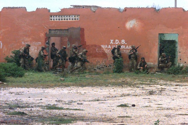 US Marines, armed with M-60 machine guns and M-16A2 rifles, conduct a building-to-building sweep of the weapons cantonment area seized in an early morning raid. As the 6:00 a.m. deadline to surrender the area was ignored, US Marines from Task Force Mogadishu surrounded and seized GEN. Aideed's weapons cantonment area in the northern part of the capital city