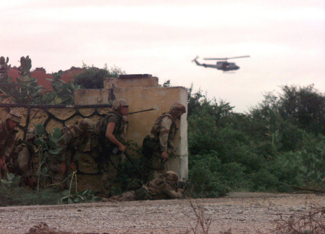 US Marines of Task Force Mogadishu prepare to storm the weapons cantonment area of Somali Warlord GEN. Aideed while a UH-1 Huey helicopter flies overhead