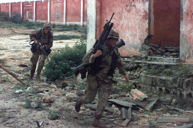 US Marines run for cover as sniper shots ring out in the compound. The Marines, armed with M203 grenade launchers attached to M16A2 rifles and an AT8 light anti-tank weapon, are attempting to secure Somali Warlord GEN. Aideed's weapons cantonment area. The Marines from Task capital city, after a 6:00 a.m. surrender deadline, were ignored by Somali nationals in the compound