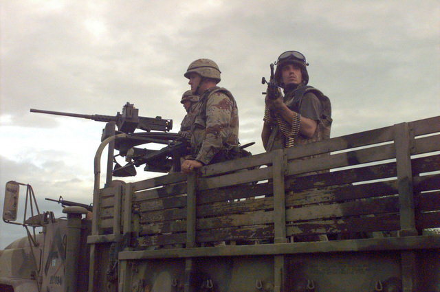 Using their truck as a vantage point, US Marines equipped with M-60 machine guns and M-16A2 rifles stay on the alert for snipers as they surround the weapons cantonment area of Somali Warlord GEN. Aideed. GEN. Aideed's compound seized by the Marines was an early morning raid