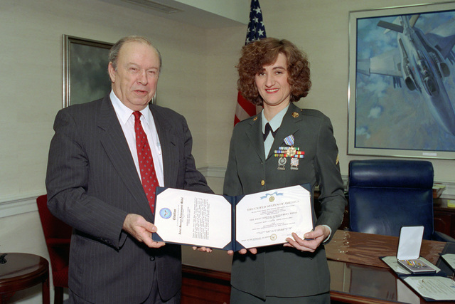 The Honorable Donald J. Yockey (left), Under Secretary of Defense for Acquisition and Technology, poses for an official photograph with U.S. Army SGT. Mary J. Carver (right) after awarding her with the Joint Service Achievement Medal in his office in the Pentagon on Jan. 13, 1993.  OSD Package No. A07D-00089 (DOD PHOTO by Helene C. Stikkel) (Released)