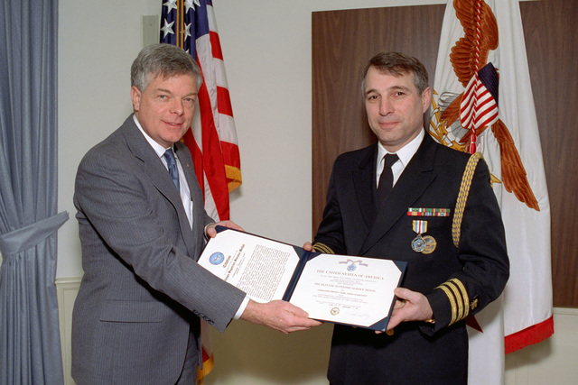 The Honorable Dr. Frayer (left), Principal Deputy Under Secretary of Defense for Acquisition, Technology, and Logistics, poses for an official photograph with U.S. Navy CMDR. Timothy J. Harp (right) after awarding him with the Defense Superior Service Medal in his office in the Pentagon on Jan. 13, 1993.  OSD Package No. A07D-00089 (DOD PHOTO by Helene C. Stikkel) (Released)
