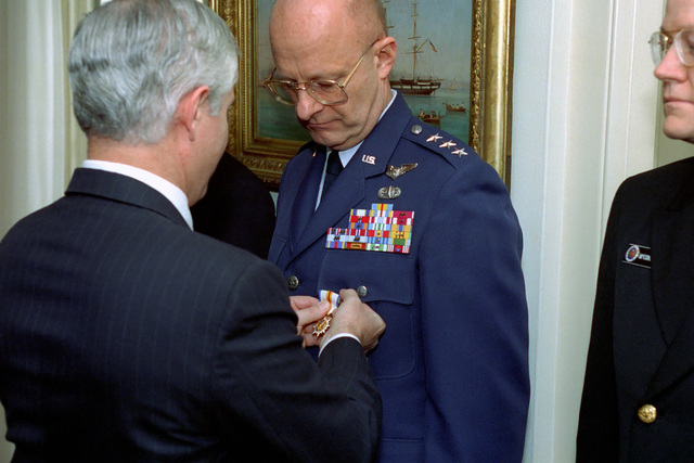 Director of the Central Intelligence Agency, Mr. Thomas Gates (foreground), presents an award to Intelligence Expert, U.S. Air Force LT. GEN. Victor E. Renuant, Commander, U.S. North American Aerospace Defense Command, on Jan. 14, 1993 at the Pentagon in Washington, D.C.  OSD Package No. A07D-00096 (DOD PHOTO by Robert D. Ward) (Released)