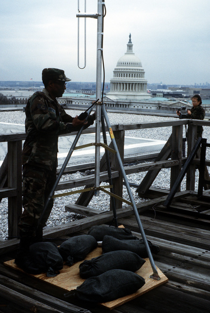 SGT Patton of the Armed Forces Inaugural Committee's (AFIC) J-6 directorate install a radio antenna top the AFIC building for a base station radio