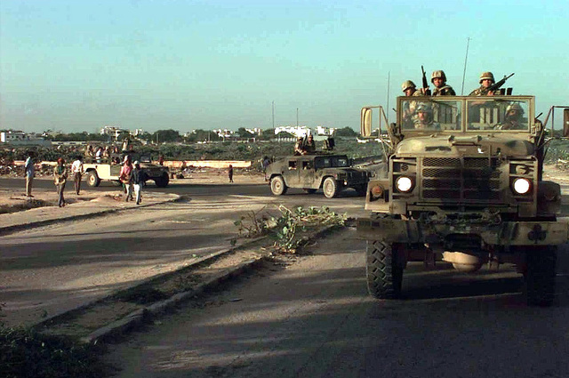 A convoy of US Marines and Army personnel leave Mogadishu Airport on an arms for food exchange mission. Leading the convoy is a head on shot of a US Marine M54 Series 5-ton Cargo Truck with Marines from Battalion Landing Team 29, 1ST Marine Expeditionary Force, Camp Pendleton, California, standing in the back carrying M16 rifles. A US Army M998 High-Mobility Multipurpose Wheeled Vehicle (HMMWV) with PSYOPS personnel talking over load speakers to the Somali people turn around a corner behind the truck. Behind the PSYOPS vehicle is a desert camouflages Humvee with armed Marines sitting in the back. This mission is in direct support of Operation Restore Hope